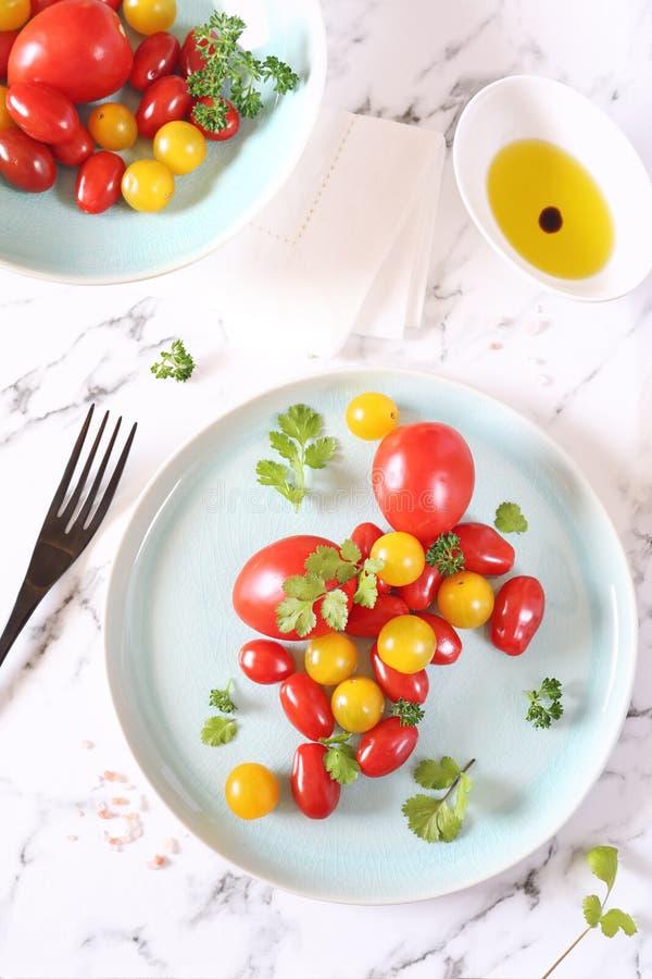 Sortiment av röda och gula körsbärsröda tomater på en blå platta, koriander och olivolja royaltyfri foto