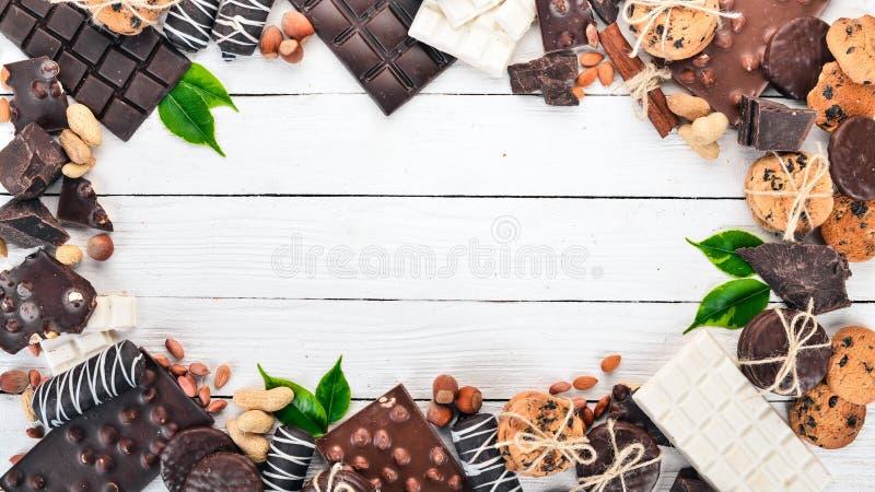 Sortiment von Schokolade mit Nüssen, Keksen und Kakao Auf weißem Holzboden stockbild