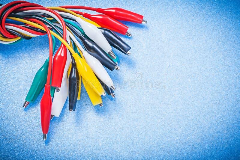 Sortimentet av det elektriska krokodilgemet kablar på blå bakgrund royaltyfria foton