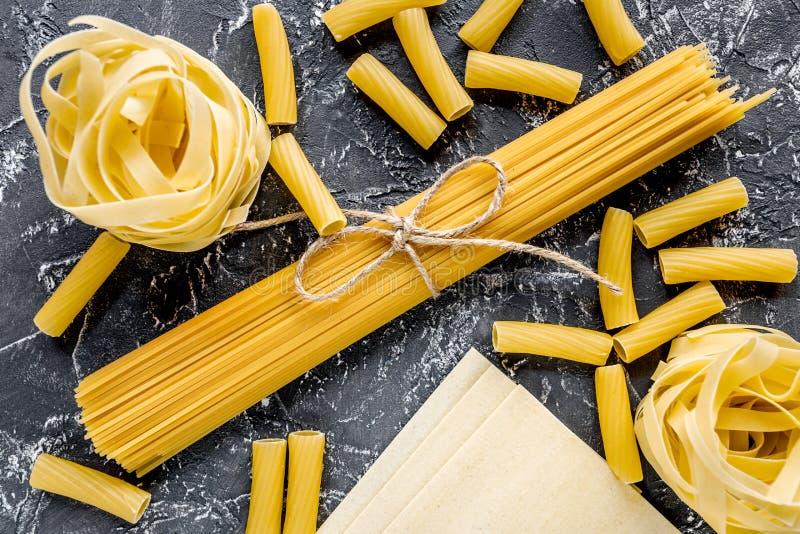 Sortimentet av italienska pastas för olik form på grå färger stenar bästa sikt för tabell arkivfoton