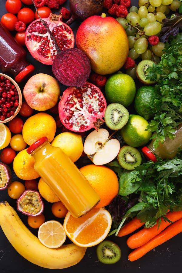 Sortimentet av olika frukter och grönsaker i regnbåge färgar med smoothies i flaskor arkivfoto