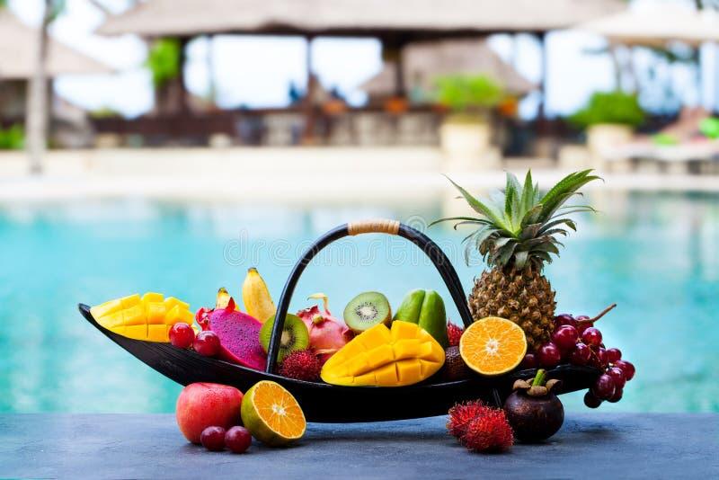 Sortimentet av tropiska frukter i träbåt Tropisk bakgrund utomhus Kopiera utrymme arkivfoton