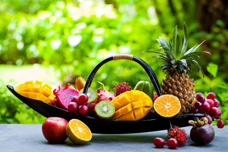 Sortimentet av tropiska frukter i träbåt Tropisk bakgrund utomhus Kopiera utrymme royaltyfria foton