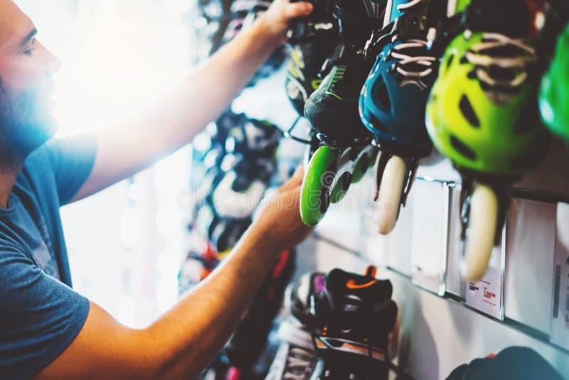 Sortimentrullskridskor i lager shoppar, personen som väljer, och att köpa färg åker rullskridskor på backgraundsolsignalljuset so arkivfoto