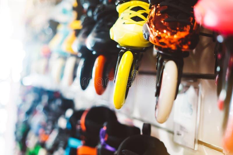Sortimentrullskridskor som isoleras i lager, shoppar, personen som väljer, och köpfärg åker rullskridskor på backgraundsolsignall arkivbild