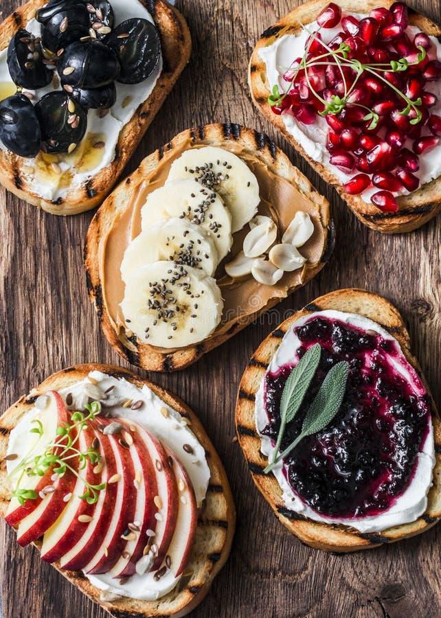 Sortimentsötsaksmörgåsar med gräddost och äpplet, granatäpplet, driftstopp, druvor, jordnötsmör, bananen, lin kärnar ur, chiaen,  royaltyfria foton