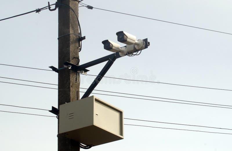 Sorveglianza della macchina fotografica sulla colonna vicino alla strada per il monitoraggio di traffico immagini stock