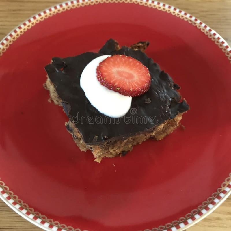 Sorvete e bolo com chocolate, creme e morangos na placa vermelha fotografia de stock