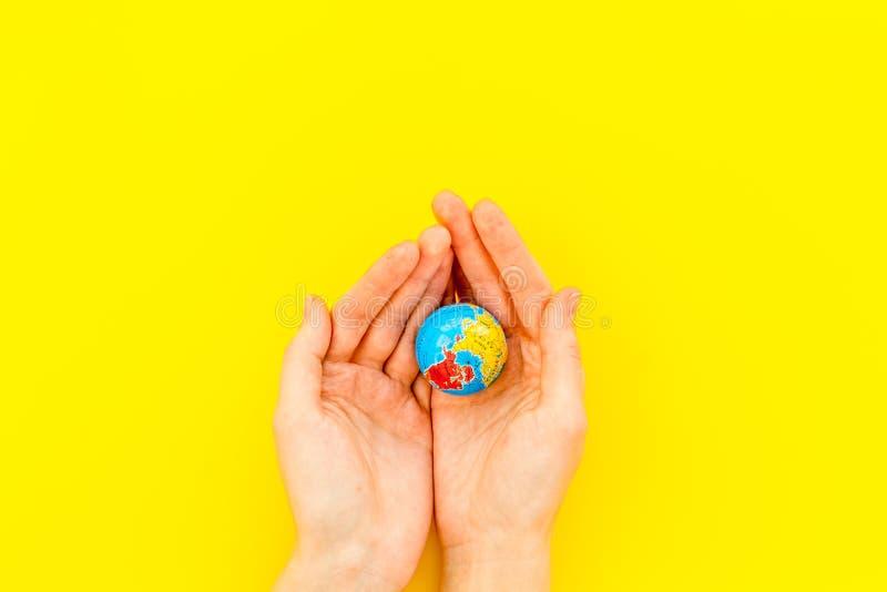 SOS Oprócz planety pojęcia Ziemia w rękach na żółtego tło odgórnego widoku mieszkania nieatutowej przestrzeni dla teksta obrazy stock