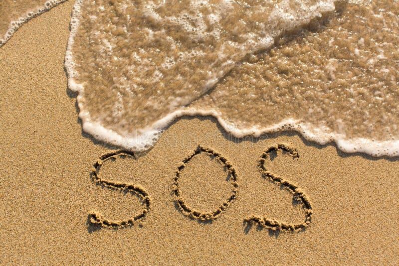 SOS - parola attinta la spiaggia di sabbia immagine stock libera da diritti