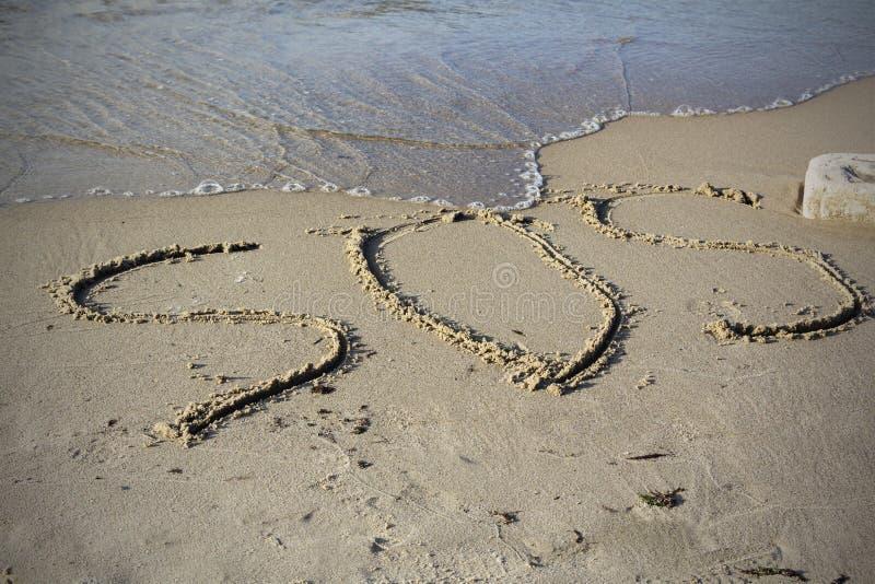 SOS - parola attinta la spiaggia di sabbia con l'onda molle immagine stock libera da diritti