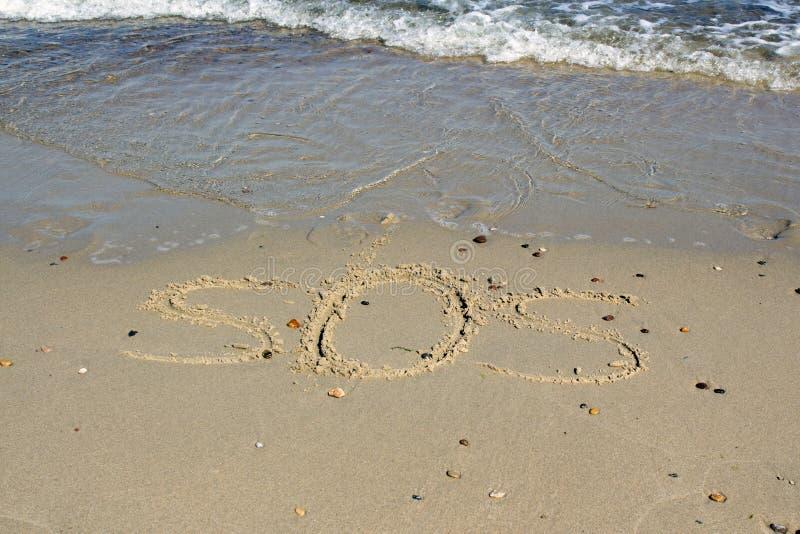 SOS - parola attinta la spiaggia di sabbia con l'onda molle immagine stock