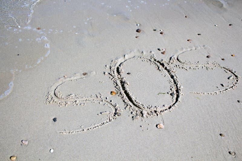 SOS - parola attinta la spiaggia di sabbia con l'onda molle fotografia stock