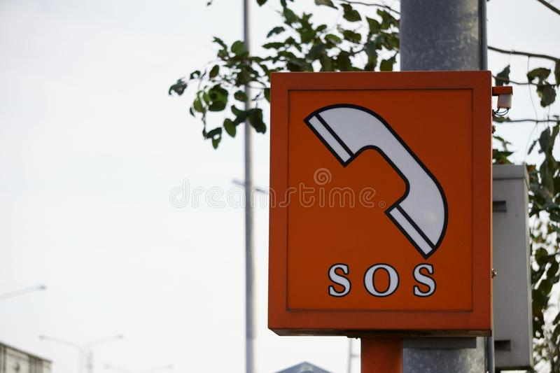 SOS phone in highway. Orange `SOS` call boxes are on all motorways, with roadside markers indicating nearer phone. Emergency telephones were installed on all stock images
