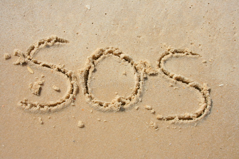 SOS in the sand stock images