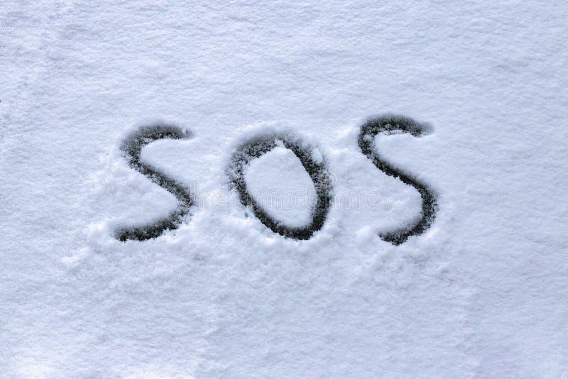 """""""SOS """"scritto nella neve fotografie stock"""