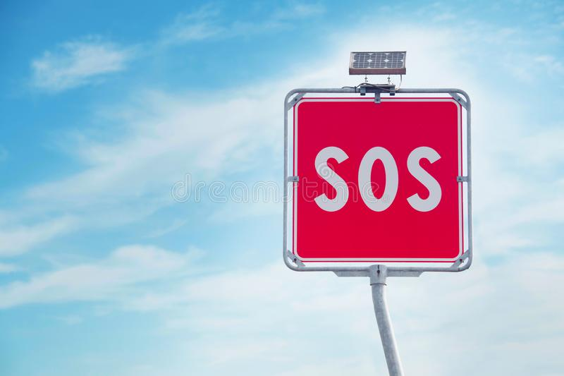 Sos sign on blue sky background. SOS sign and phone box on highway in Italy.  royalty free stock photos