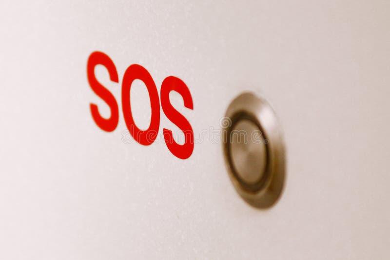 SOSbadrumnödknapp på väggen royaltyfri bild