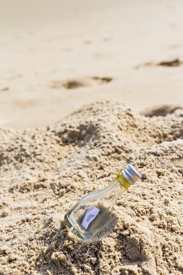 SOSmeddelande i flaska på stranden royaltyfria bilder