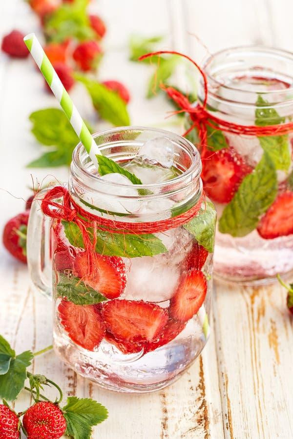 Sosowana woda z świeżymi truskawkami i mennicą w szklanych słojach zdjęcia royalty free