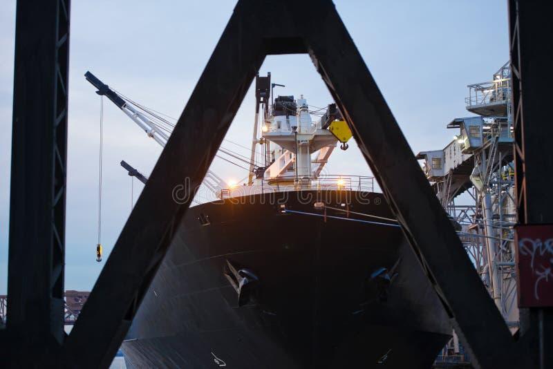 Sospeche el buque de carga negro grande de la cubierta anclado en la descarga para el downloa foto de archivo