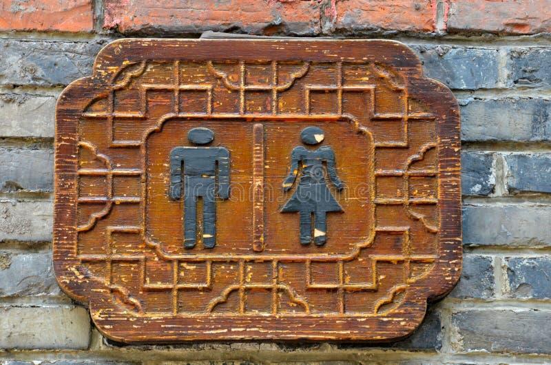 Sospiro femminile maschio delle toilette della toilette sul muro di mattoni immagine stock libera da diritti