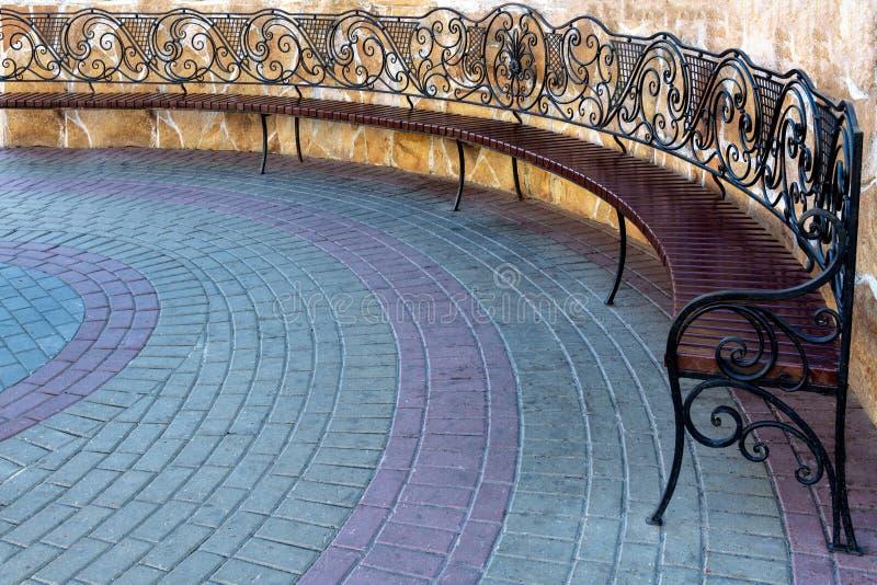 Sostegni per banchi forgiati Openwork del metallo sul marciapiede nel parco della città immagine stock