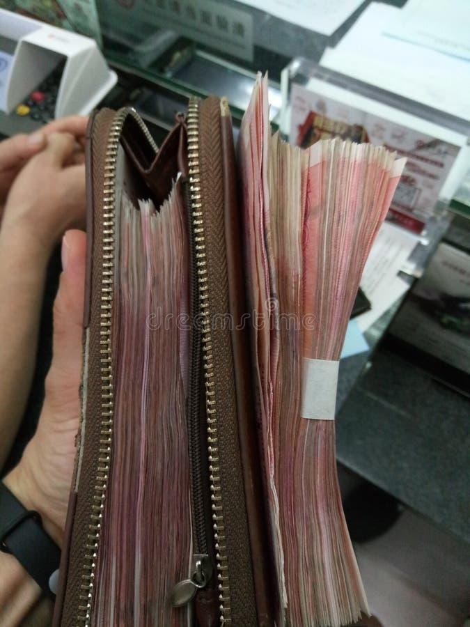 Sostener el dinero y el monedero en mi mano imagen de archivo