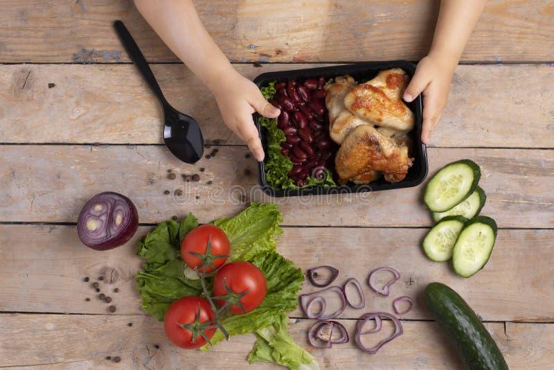Sostener el envase de comida plástico negro Pepino y cebolla con los tomaoes fotos de archivo libres de regalías
