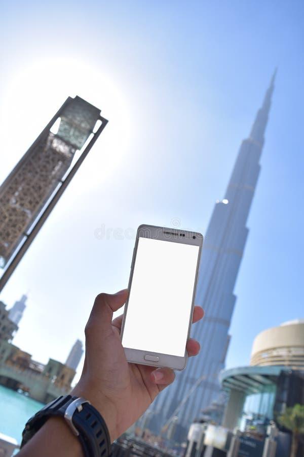 Sostener el teléfono blanco con el fondo de Burj Khalifah fotografía de archivo libre de regalías