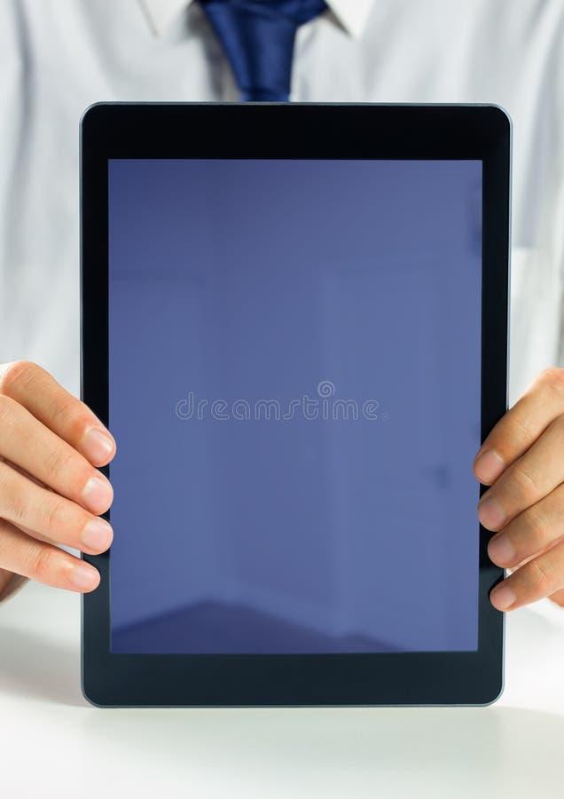 Sostener la tableta de la pantalla en blanco con el hombre de negocios imagen de archivo libre de regalías
