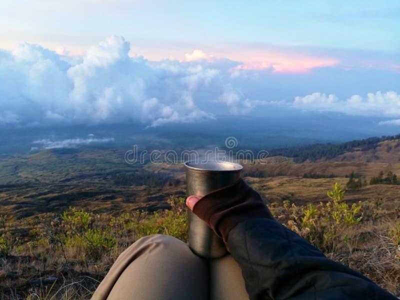 Sostener la taza de té caliente durante tiempo de la salida del sol en las montañas imagenes de archivo
