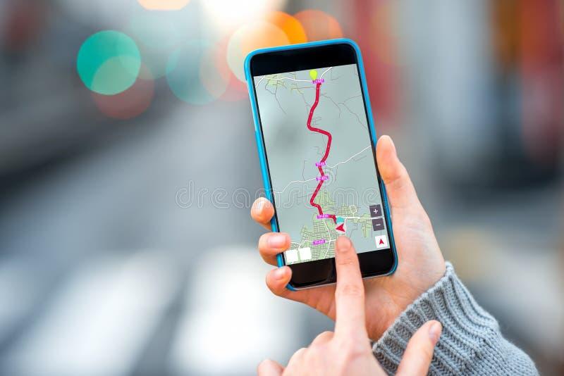 Sostener Smartphone en el fondo de la ciudad imagen de archivo