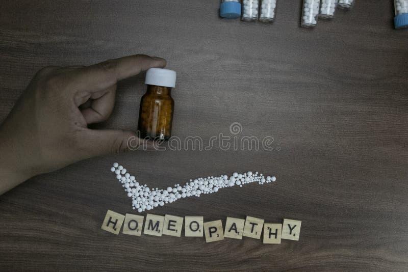 Sostener una botella líquida de la sustancia en una mano con una marca de verificación y texto homeopático en el fondo de madera fotografía de archivo