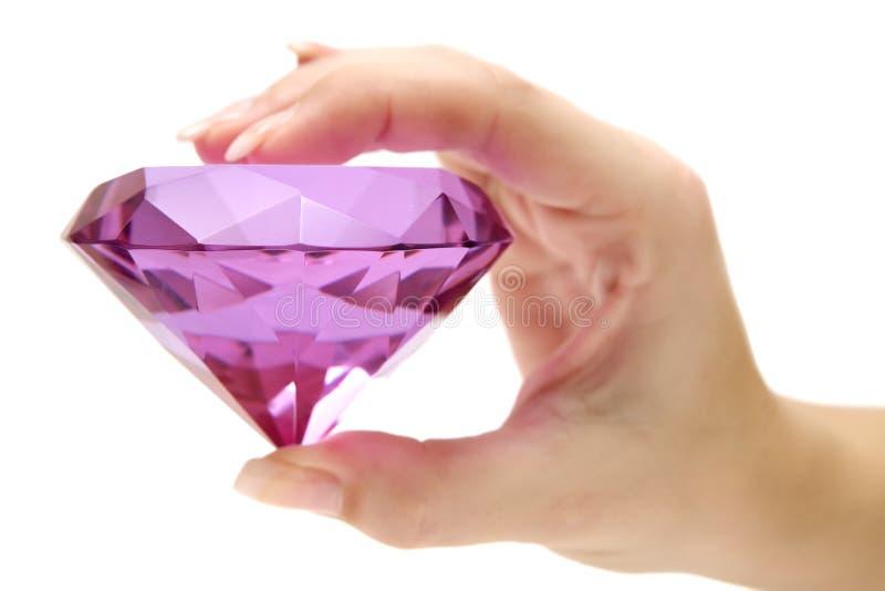 Sostener una piedra preciosa rosada fotografía de archivo libre de regalías