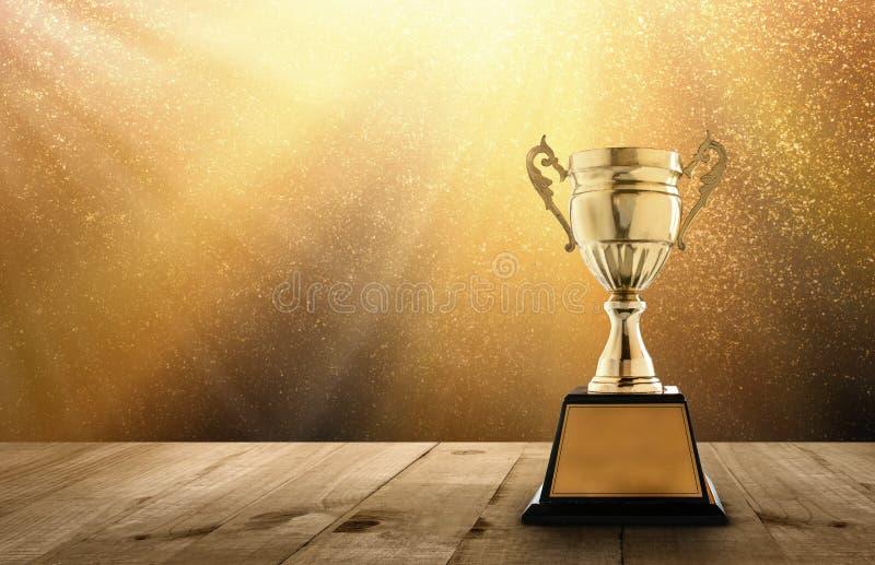 sostenga il trofeo dorato sulla tavola di legno con lo spazio della copia e l'oro TW immagine stock