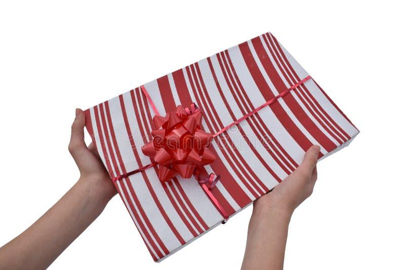 Sosteniendo el regalo rojo y blanco aislado en blanco fotografía de archivo