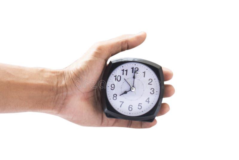Sosteniendo el reloj en fondo aislado el 12:00 o P.M. del tiempo y fotos de archivo libres de regalías