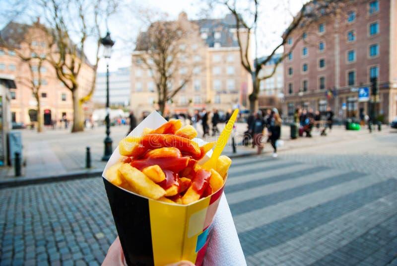 Sosteniendo las fritadas típicas del belga disponibles en Bruselas imágenes de archivo libres de regalías