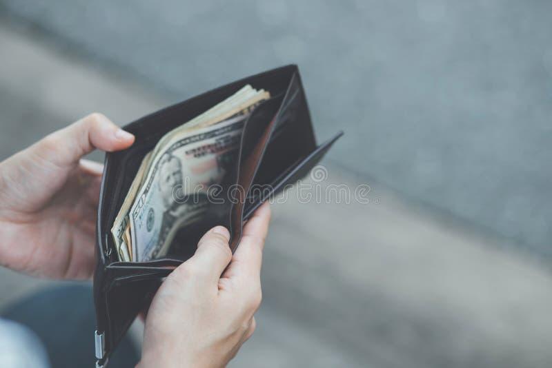 Sosteniendo una cartera en las manos de un hombre para sacar el dinero del bolsillo imagen de archivo libre de regalías