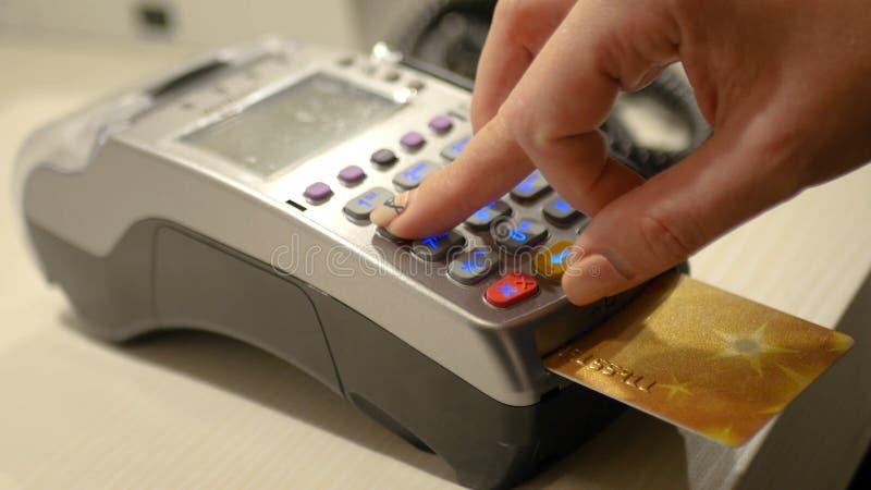 Sostiene una tarjeta a través del terminal del banco HD imágenes de archivo libres de regalías
