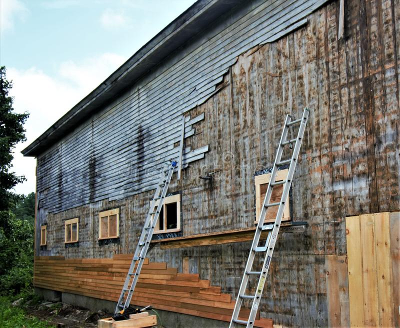 Sostituendo il vecchio, raccordo grigio di vecchio granaio di legno con il nuovo raccordo marrone di abbronzatura immagine stock