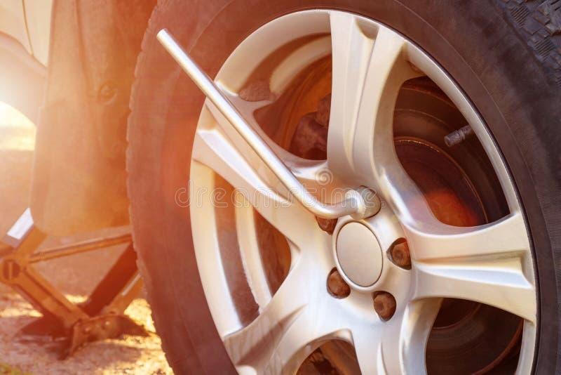 Sostituendo le ruote sulla strada principale, svitante i dadi con una chiave immagini stock