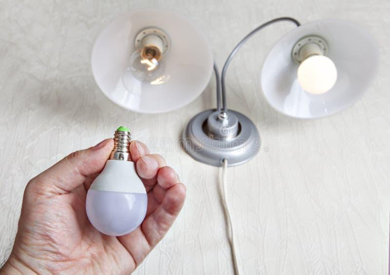 Sostituzione della lampada incandescente a favore del LED fotografia stock libera da diritti