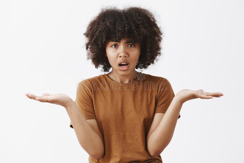 Sot талии-вверх confused интенсивной и надоеданной Афро-американской молодой женщины с вьющиеся волосы в ультрамодной коричневой  стоковое изображение rf