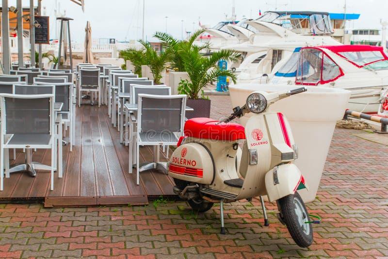 SOTCHI, RUSLAND, 18 APRIL 2019 - de scooter parkeerde dichtbij het restaurant op de achtergrond van de zeehaven en de jachten royalty-vrije stock fotografie