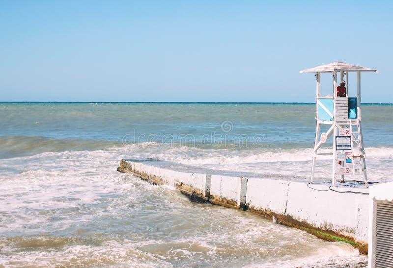 Sotchi, Rusland - Augustus, 05, 2019 Witte cabinetoren met badmeester op kust van de stormende Zwarte Zee, leeg strand royalty-vrije stock fotografie