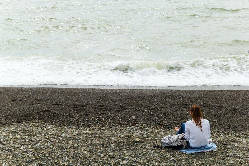 SOTCHI, RUSSIE, LE 20 AVRIL 2019 - jeune fille seule s'asseyant de nouveau à la caméra sur la plage et regardant la mer images stock