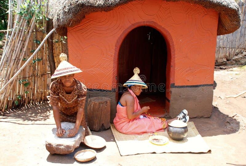 Sothovrouwen bij stammenhuis in het Culturele Dorp van Lesedi, Zuiden Afr stock foto's