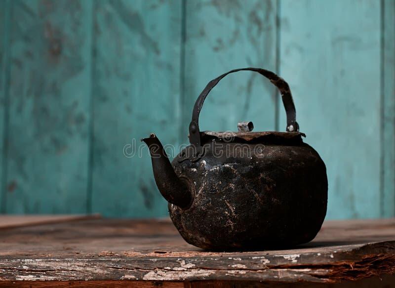Sotig gammal teapot på den gammala tabellen i kök fotografering för bildbyråer